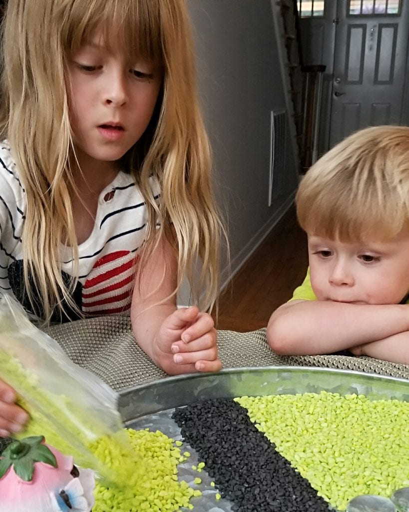 girl pouring green Dollar Tree pebbles