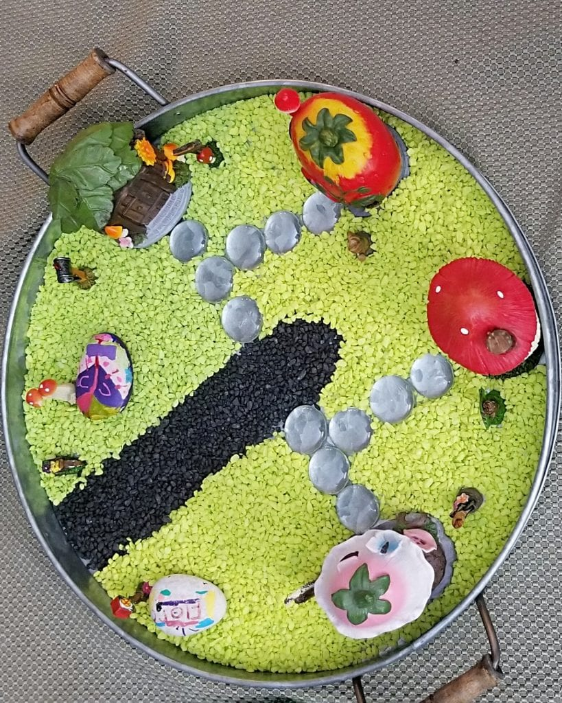 Easy fairy garden project on a circle metal tray with green pebble grass