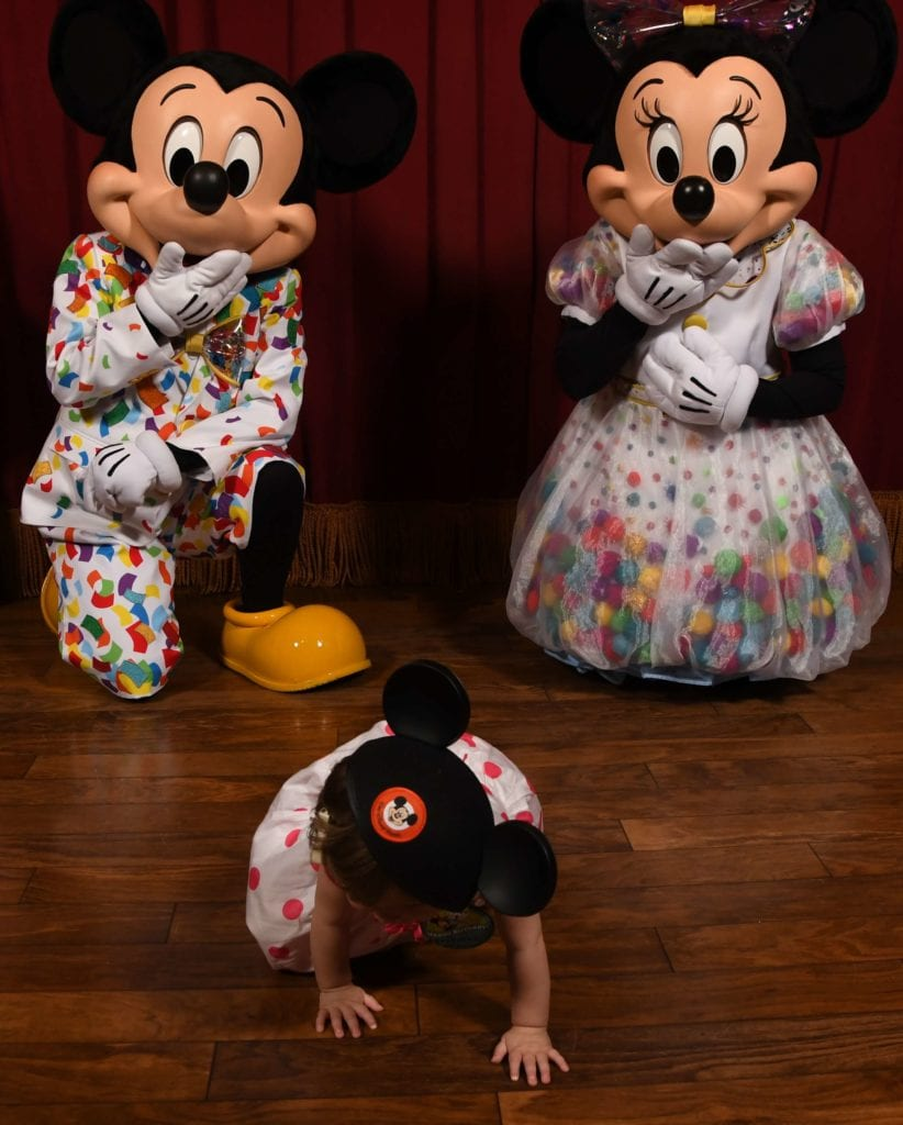 Mickey Mouse and Minnie Mouse at Magic Kingdom Disney World With a 1 Year Old runaway baby wearing Mickey ears. Funny Disney baby picture.