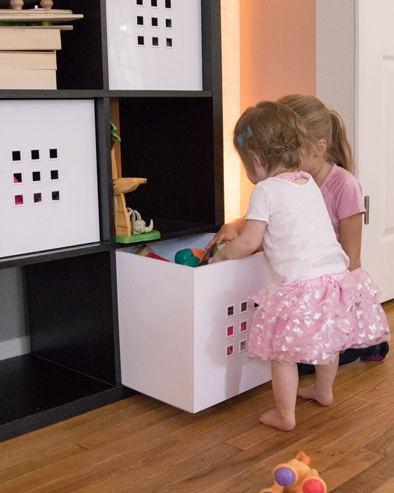 Quick clean your house with storage furniture like cube shelves these girls are using to put toys in.
