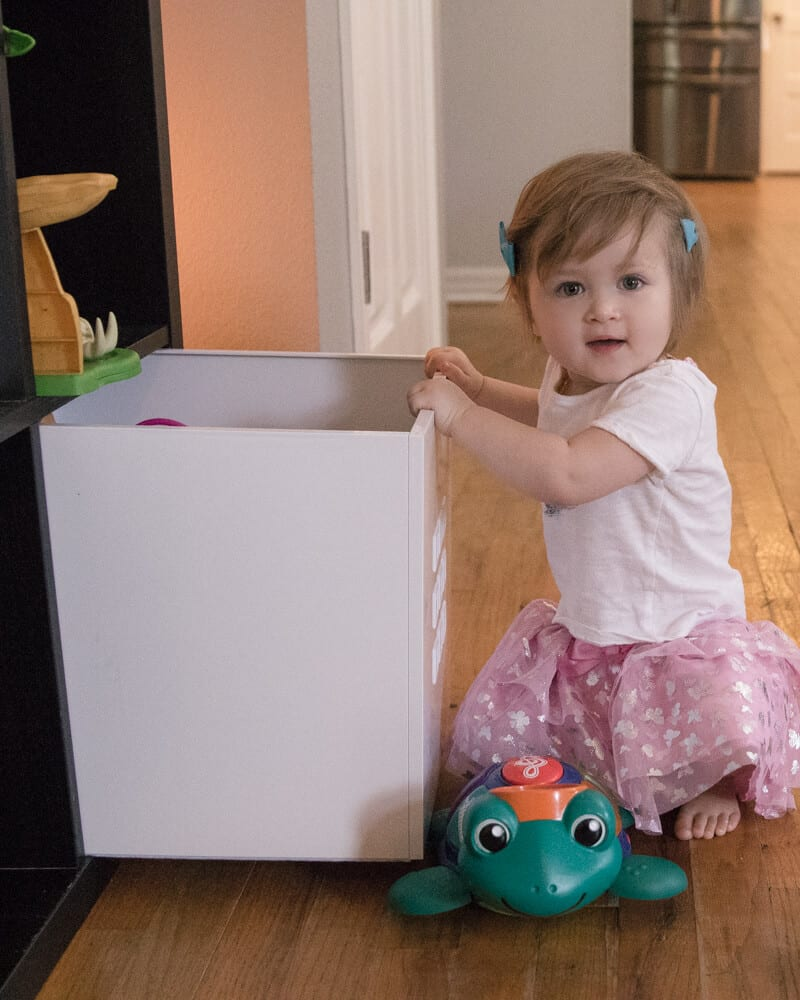 Baby girl in pink skirt playing with a white plastic cube storage box that helps to quick clean your house