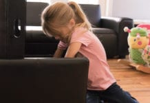 Girl putting toys away in a storage ottoman to quick clean your house