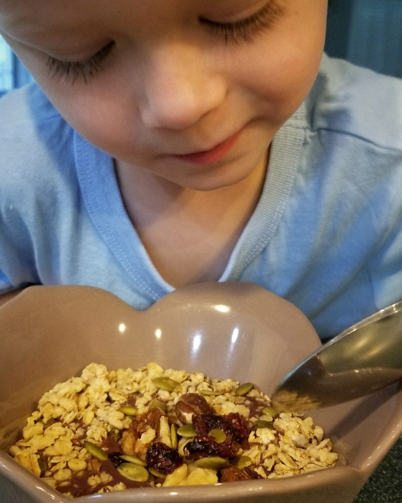 boy eating acai berry bowl for a healthy breakfast for kids that is easy